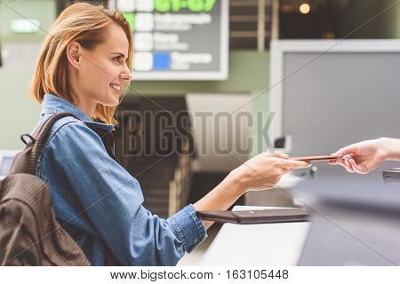 Excited young woman is showing her documents to check-in attendant. She is standing and smiling