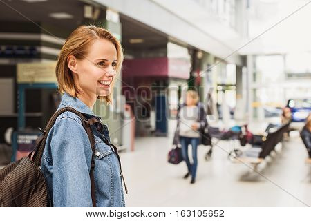 I am ready for travel. Joyful young woman is standing at airport hall and smiling. She is carrying backpack