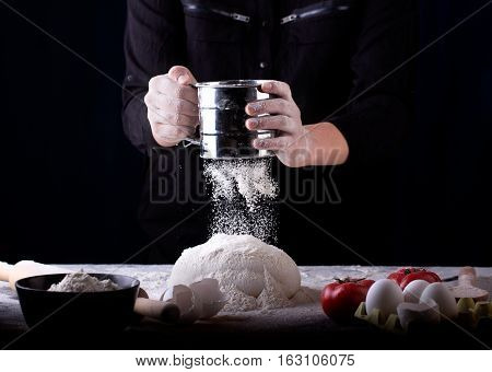 Baker prepares the dough on table. Female hands sifting flour from sifter. Concept of baking and patisserie.