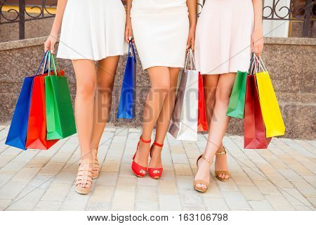 Close Up Of Three Women With Shopping Bags Showing Their Legs