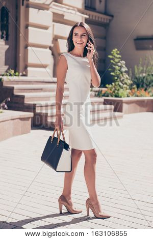Happy Young Business Woman Talking On Phone While Walking On The Street