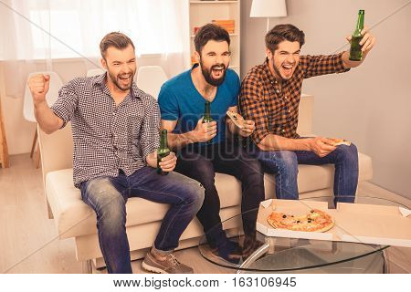 Goal!  Happy Joyful Men Sitting On Sofa And Watching Sport Tv With Beer And Pizza