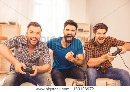 Portrait Of Excited Laughing Men Playing Video Games