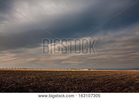 Plowed field in autumn. Works in the country field