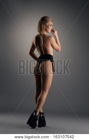 Sexy blonde with short hair cut in black underwear and high heel platform poses topless with her back to viewer in studio