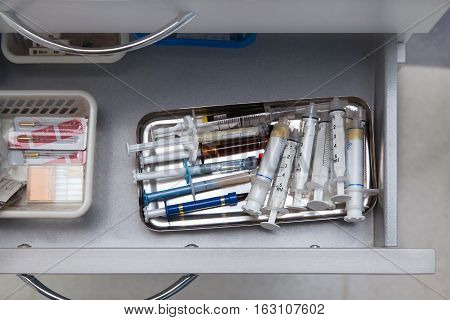 Dentist tools drawer with various syringes in a drawer