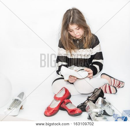 boring tired little girl sitting and trying to chose a shoes for her