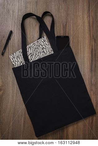Black blank cotton eco tote bag with smartphone and notebook design mockup.