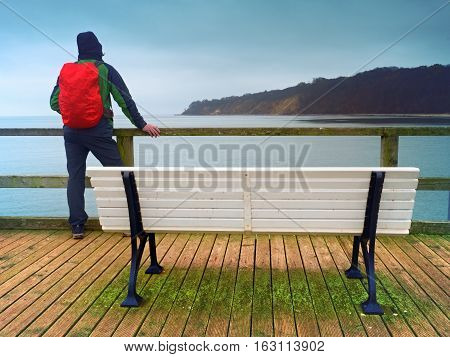 Man Tourist With Red Backpack On Wooden Sea Pier. Autumn Rainy Day.