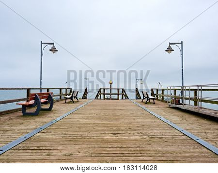 Adult Tall Man On Pier Board Look Over Sea To Morning Fall Horizon. Smooth Water Level