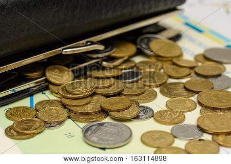Money. Black leather purse with scattered coins.