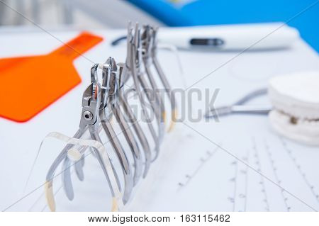 Close up Orthodontist Dental set of clamps and pliers and other tools on the working table surface poster
