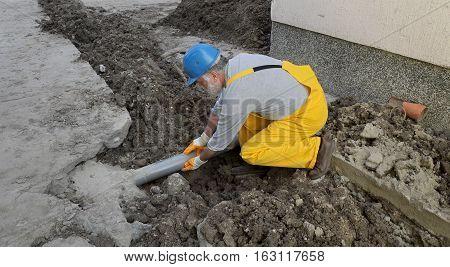 Plumber At Construction Site Repair Sewerage Tube