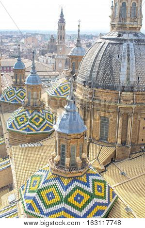 Top view of the domes and roof tiles from the tower of of Cathedral-Basilica of Our Lady of the Pillar on a summer day, Zaragoza, province Aragon, Spain