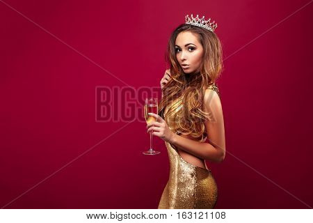 Portrait of young adorable girl wearing golden dress and crown with gems posing with glass of champagne on red background