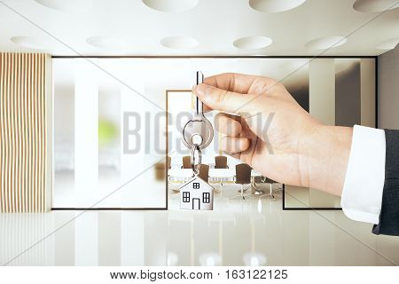 Hand holding key with house keychain in conference room interior. Real estate concept. 3D Rendering