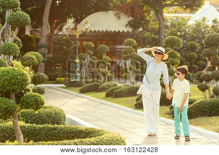 Young mother and her little son walking in Green bonsai trees gardens in Wat Arun, Bangkok, Thailand