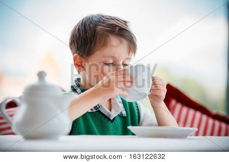Cute little boy drinking tea in cafeteria