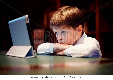 Cute little boy with a tablet pc indoors. Internet addiction and people concept