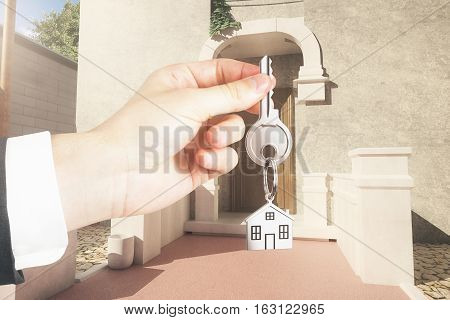 Hand holding key with house keychain on creative italian exterior background. Property concept. 3D Rendering