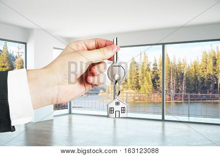 Hand holding key with house keychain in concrete interior with panoramic landscape view. 3D Rendering. Real estate concept