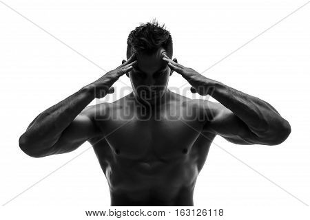 The beautiful and strong young guy holding head with two heands. Pain. Black and white photo, silhouette. Hidden in the shadow.  Male silhouette.