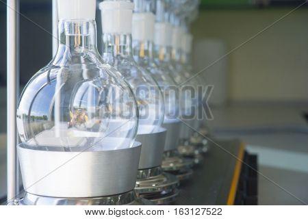 Laboratory equipment glass bottles round bottom flask on heating mantle Soxhlet Extraction