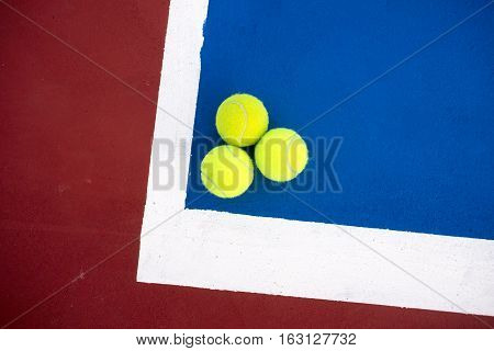 Old three tennis balls on tennis court.