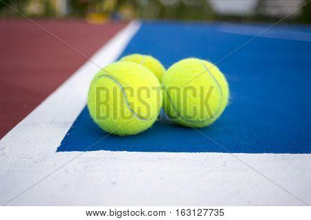 Old three tennis balls on tennis court.