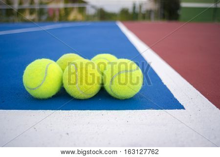 Old five tennis balls on tennis court.