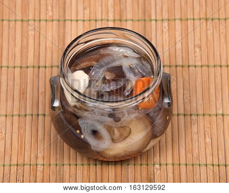 Shiitake marinated mushrooms in jar isolated on bamboo placemat