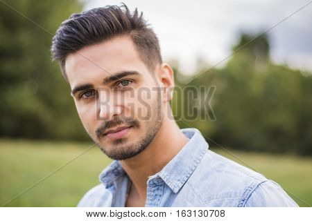 Handsome young man at countryside, in front of field or grassland, wearing shirt, looking away to a side