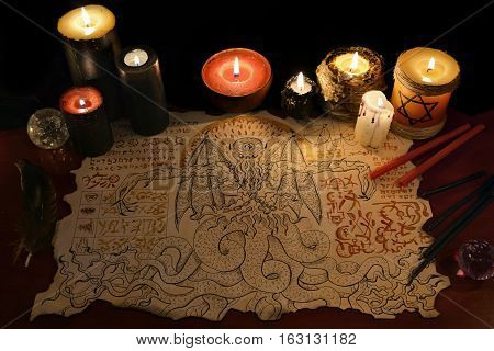 Black magic ritual or spell with demon manuscript and evil candles. Halloween concept. Occult objects on table. There is no foreign text in the image, all symbols are imaginary and fantasy ones