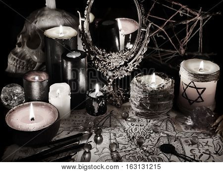 Mystic still life with magic mirror, demon paper and candles in grunge vintage style. Esoteric objects on table. There is no foreign text in the image, all symbols are imaginary and fantasy ones