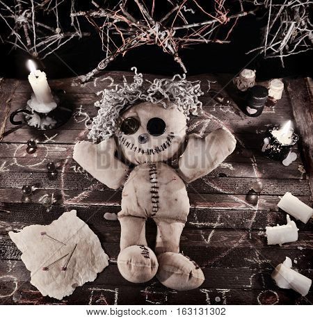 Voodoo ritual with doll and magic objects in vintage grunge style. Halloween background, black magic rite or spell with occult and esoteric symbols
