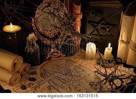Mystic still life with demon manuscript, candles and magic book. Halloween concept. Esoteric objects on table. There is no foreign text in the image, all symbols are imaginary and fantasy ones