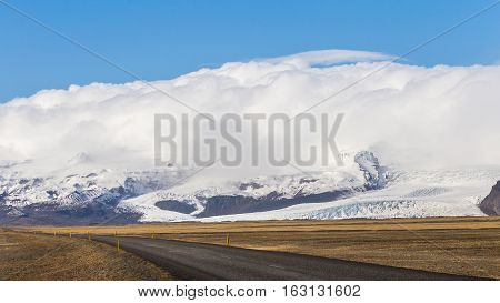 The ring road passes by a tongue of the Vatna Glacier in South Iceland while clouds creep up over the snowcapped summit of the Hvannadalshnukur mountain