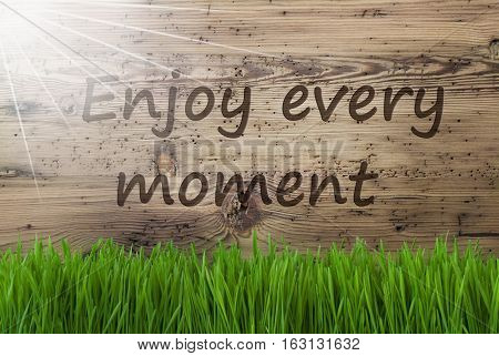 English Quote Enjoy Every Moment. Spring Season Greeting Card. Sunny Aged Wooden Background With Gras.
