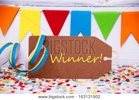 Brown Label With English Text Winner. Party Decoration Like Streamer And Confetti. White Wooden Background. Greeting Card For Celebrations
