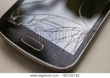 broken touchscreen mobile phone lying on the wooden table