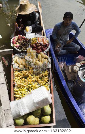 BANGKOK, THAILAND - November 5, 2016: Woman selling a variety of fresh fruit on the floating market in Bangkok Thailand