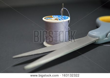 A threaded needle and scissors on a black background