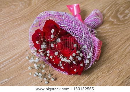 a bouquet of red roses on a wooden background