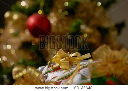 Stacks Of Christmas Presents Under A Christmas Tree With Defocused Lights