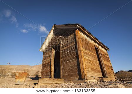 Old abandoned shack at Rhyolite Ghost Town in the Nevada Desert in early morning light with clear blue skies.