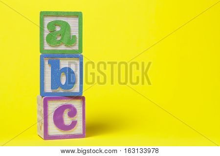 ABC Alphabet blocks stacked up on yellow background
