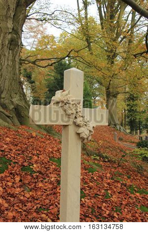A decorated grave ornament tombstone on a autumn graveyard