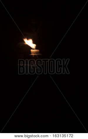 A single candle flickering on a black background