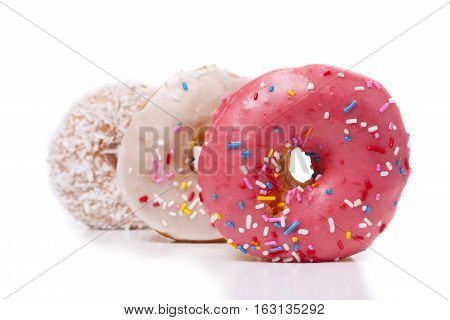 Three donuts isolated on White Background. Pink Frosted and Coconut with sprinkles.