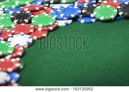 Background poker chips creating a border with green felt copy space. Shallow Depth of Field with one chip in focus.